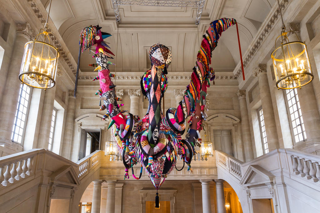 Multicolored large-scale installation by Joana Vasconcelos in an ornate interior.