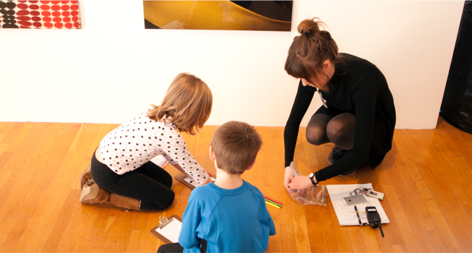 Museum attendant crouches next to children seated in the museum and helps them draw.