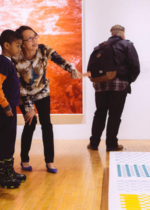 Director Lisa Tung points out artistic detail to a young student in the museum.