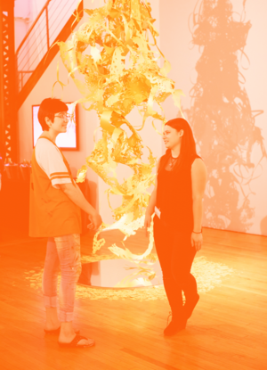 A student gallery attendant speaks with another student in front of a tall laser-cut sculpture.